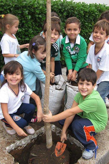 Alunos plantando árvore na frente da Unidade Infantil.